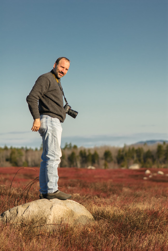 Paul standing on a rock with blueberry field behind him